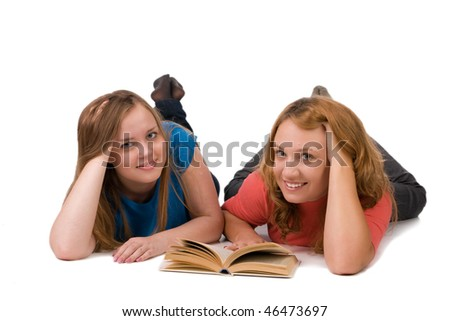 Two beautiful girls lying on the floor with a book, isolated on white - stock photo