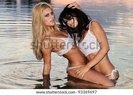Two beautiful girls posing in the warm water at sunset - stock photo