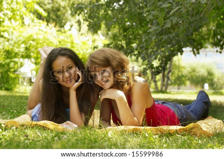 two beautiful girls sit in park - stock photo