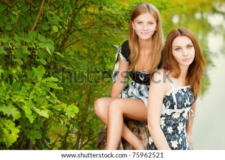 Two beautiful girls sit on stub about pond in summer city park. - stock photo