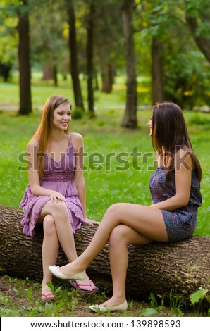 Two beautiful girls sitting in the park and talking on beautiful summer day. - stock photo