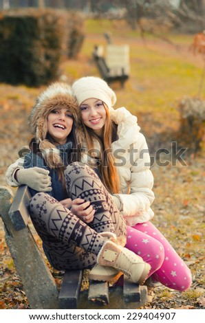 Two beautiful girls sitting on the bench outdoor on sunny autumn day. - stock photo