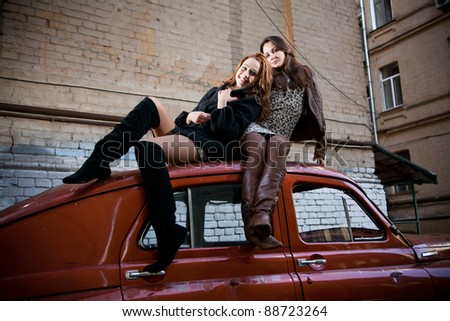 Two beautiful girls sitting on top of retro car - stock photo