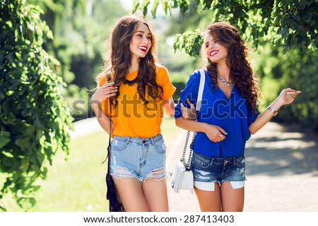 Two beautiful  girls walking in  the  summer park end talking.  Friends wearing stylish shirt and jeans shorts , enjoying  day off and have fun. - stock photo