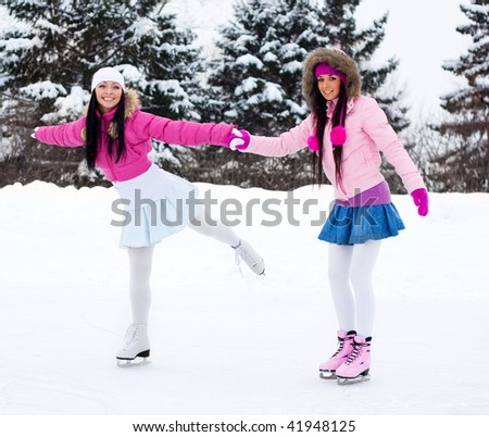 two beautiful girls wearing warm winter clothes ice skating - stock photo