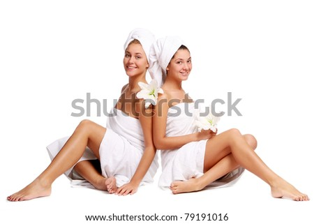Two beautiful girls with towels and flowers relaxing in spa - stock photo