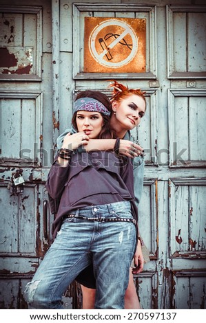 Two beautiful grunge girls standing at a wall - stock photo