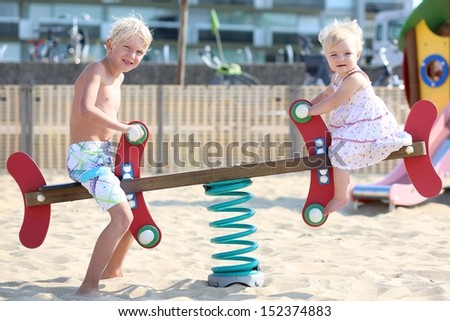 Two beautiful happy blond children, teenager boy and his little baby sister, playing together at outdoors sandy beach playground rocking on a spring seesaw swing - stock photo