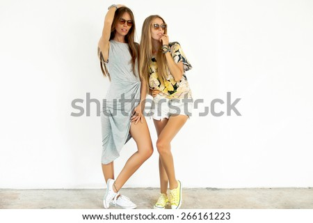 Two beautiful happy friends in sunglasses and  summer clothes pose on white background.Young active people.Sisters having  fun.Fashion look of  summer best friend girls relaxing  in summer day. - stock photo