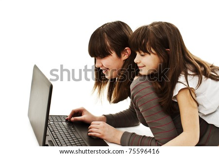 Two beautiful happy girls using a laptop against white background - stock photo