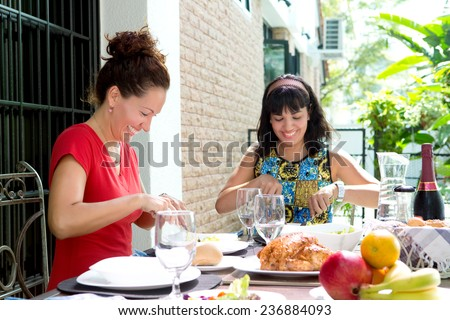 Two beautiful hispanic women enjoying an outdoor home meal together. Concept of family togetherness and outdoor dining. - stock photo