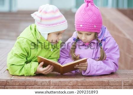 Two beautiful little girls in coats reads orange book. - stock photo
