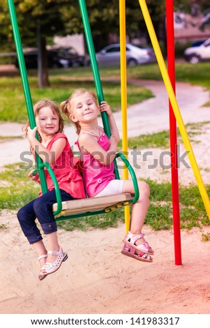 Two beautiful little girls on a swings outdoor in the playground at summertime - stock photo