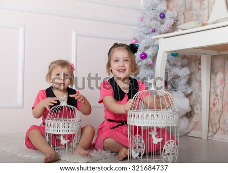 Two beautiful little girls sitting on   floor with   bird cages.  - stock photo