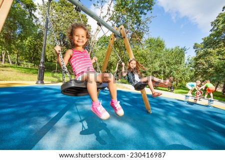 Two beautiful little girls swinging on swings on playground with smile on sunny summer day - stock photo