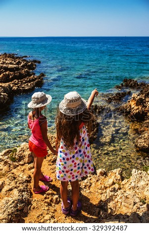 Two beautiful little sisters on the rocky shores of the Adriatic Sea in Croatia. - stock photo