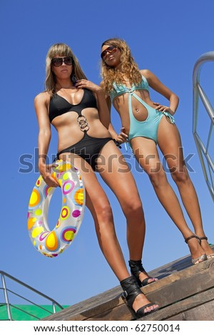 Two beautiful models in swimsuit, with multicolored inflatable ring - stock photo