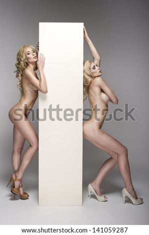 Two beautiful naked women with board  - stock photo