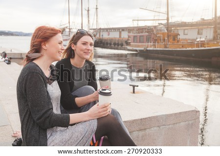 Two beautiful nordic girls at Oslo harbour enjoying life, talking and looking at smart phone, with ships on background. They also hold a cup of coffee in the hands. Lifestyle and friendship concepts. - stock photo