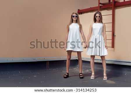 two beautiful sexy young woman in fashionable white dress posing on a roof with sunglasses in the bright summer day - stock photo