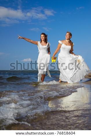 two beautiful slavonic brides walking along coastal strip - stock photo