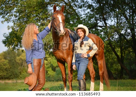 Two Beautiful Smiling Cowgirls with horse - stock photo