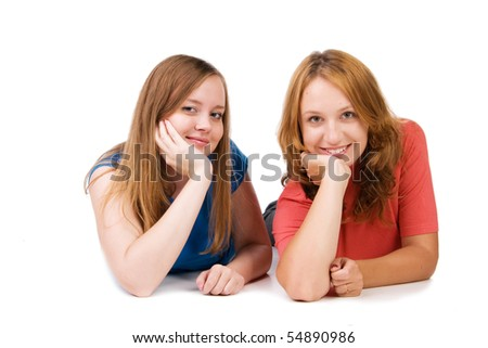 Two beautiful smiling girls lie on a floor, isolated on white - stock photo