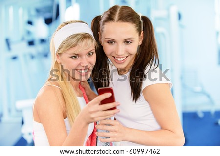 Two beautiful smiling sportswomen read sms on phone in big sports hall. - stock photo