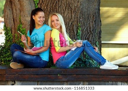two beautiful smiling students study on bench under an old oak tree - stock photo