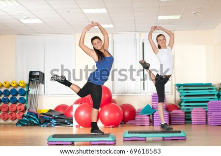 Two beautiful sport woman doing stretching fitness exercise at sport gym. Step. - stock photo