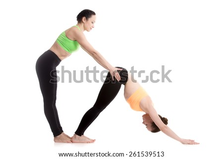 Two beautiful sporty girls practice yoga with partner, coach helps student, stretching in downward-facing dog yoga pose, adho mukha svanasana - stock photo