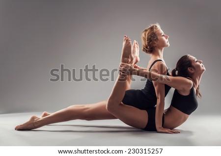 Two beautiful sporty women are doing yoga asanas. Urdhva Mukha Svanasana, Dhanurasana - stock photo
