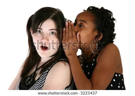 Two beautiful thirteen year old girls sharing a secret. - stock photo