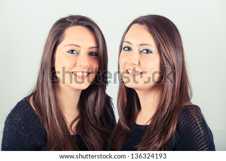 Two Beautiful Twin Sisters Embraced - stock photo