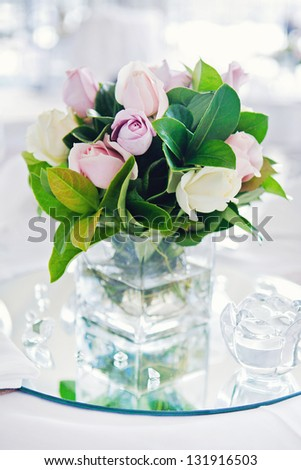 Two beautiful wedding rings on a background of a bouquet of roses - stock photo
