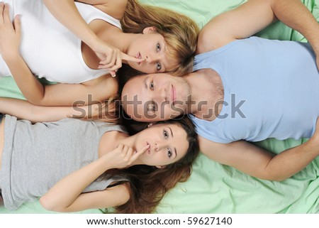 Two beautiful women and man lying on the bed - stock photo
