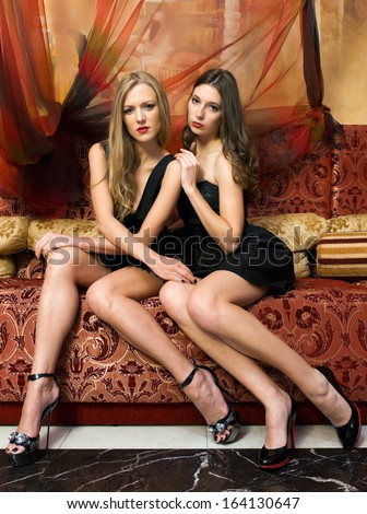 Two beautiful women are sitting on the sofa in a oriental interior - stock photo