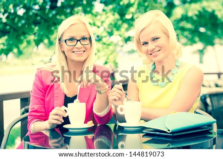 Two Beautiful Women Drinking Coffee at Bar - stock photo