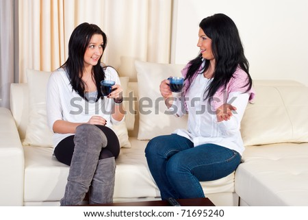 Two beautiful women having conversation  drinking coffee and sitting on couch home - stock photo