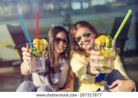 Two beautiful women having fun in a bar - stock photo