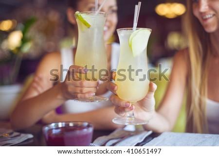 Two beautiful women having fun in a bar drinking cocktails - stock photo