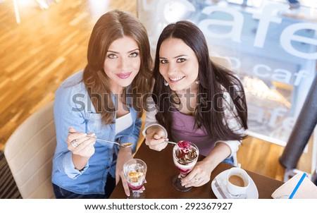 Two beautiful women in a cafe having fun - stock photo