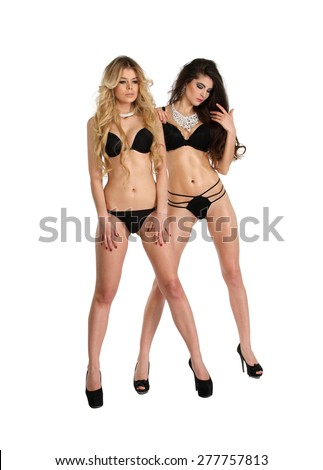 Two beautiful women in black erotic lingerie isolated on white background - stock photo