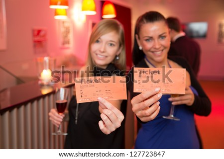 Two beautiful women presenting tickets for a theater, cinema or a concert - stock photo