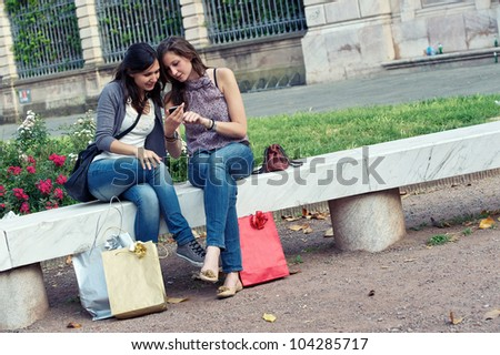 Two Beautiful Women Sending Messages with Mobile - stock photo