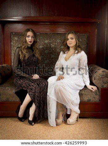 Two beautiful women sitting on vintage sofa at old house - stock photo