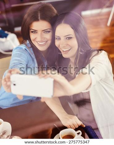 Two beautiful women taking selfie in cafe - stock photo