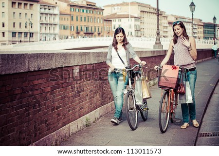 Two Beautiful Women Walking in the City with Bicycles and Bags,Italy - stock photo