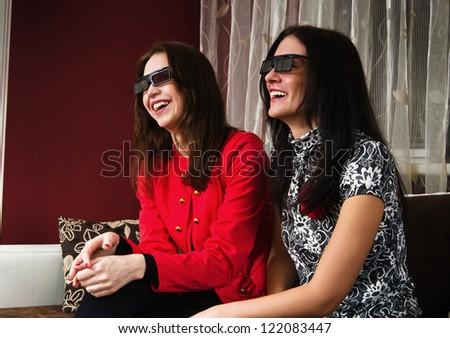Two beautiful women watching 3D TV at home - stock photo