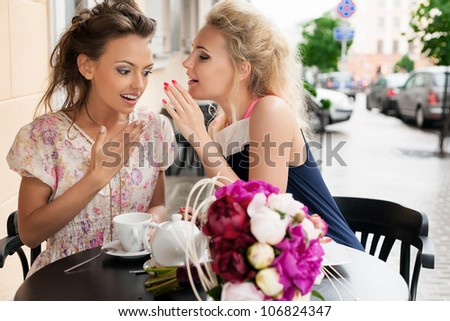 Two beautiful women with great smile and hairstyle whispering. - stock photo